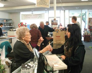 Generous Auxiliary:  Today, the Pasadena Auxiliary operates a thrift store in nearby Altadena.  Proceeds benefit the programs of Boys Republic and Girls Republic.  In the photo above, an Auxiliary member assists a Girls Republic student.